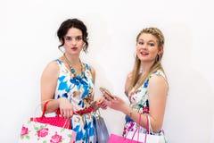 Två modeller som står med shoppingpåsar och, ilar telefonen arkivbild