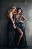 Två modemodeller i lång svart klär med kronor Arkivbild
