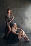 Två modemodeller i lång svart klär med kronor Royaltyfria Bilder