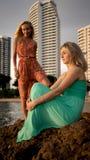 Två modemodeller som poserar i rött och turkos, klär i strålarna av inställningssolen på den tropiska stranden på en bakgrund Royaltyfri Foto
