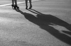 Två moderna flickor på höga häl står på solig asfalt Royaltyfri Foto