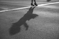 Två moderna flickor på höga häl står på solig asfalt Royaltyfria Foton