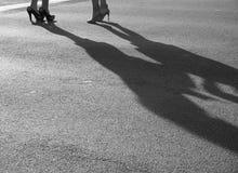 Två moderna flickor på höga häl står på solig asfalt Royaltyfri Bild