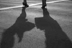 Två moderna flickor på höga häl står på solig asfalt Arkivfoto