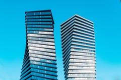 Två moderna högväxta affärsskyskrapor med lotten av exponeringsglasfönster mot blå himmel - bild arkivfoto