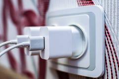 Två moderna vita mobiltelefonuppladdare pluggade in i håligheten Förlorat begrepp för energi Arkivfoto