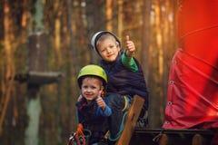 Två modiga förtjusande pojkar, dubbel stående, sitta för ungar och smil Royaltyfri Foto