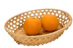 Två mogna apelsiner i en vide- platta Arkivbild