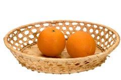 Två mogna apelsiner i en vide- platta Arkivfoto