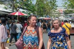 Två mogna damer för westerner verkar för att vara vännen som tillsammans går och talar i Chatuchak helgmarknad royaltyfria bilder