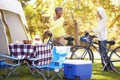 Två mogna kvinnor som rider cyklar på campa ferie Fotografering för Bildbyråer