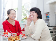 Två mogna kvinnor som skrattar på köksbordet Royaltyfri Fotografi