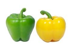 Två mogna ljusa färgspanska peppar, en gräsplan och en guling som isoleras på vit bakgrund Fotografering för Bildbyråer