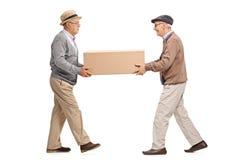 Två mogna män som bär en stor kartong royaltyfria bilder