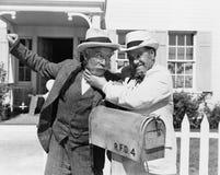 Två mogna män som framme slåss nära en brevlåda av ett hus (alla visade personer inte är längre uppehälle, och inget gods finns s Arkivfoton