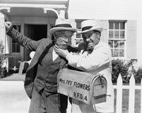 Två mogna män som framme slåss nära en brevlåda av ett hus (alla visade personer inte är längre uppehälle, och inget gods finns s Arkivfoto