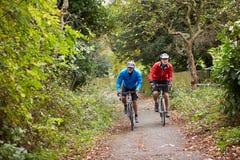 Två mogna manliga cyklister som rider cyklar längs banan Arkivbild