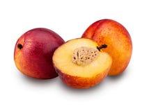 Två mogna nektarinfrukter och en klippte i halva royaltyfria foton