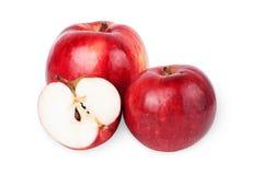 Två mogna röda äpplen och halva av äpplet. på en vitbackg arkivfoto