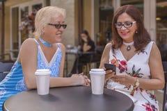 Två mogna vänner tycker om kaffe utomhus, medan se smartphonen fotografering för bildbyråer