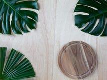 Två monsterasidor och palmblad, skärbräda för runt trä på den wood bakgrunden royaltyfri bild