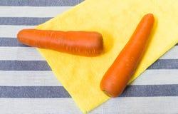Två morötter som förläggas på gult mjukt tyg med randig bakgrund Arkivfoto