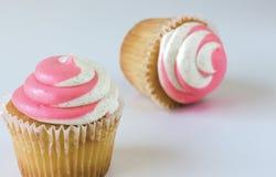 Två muffin med rosa färg- och vitvirvelisläggning på vit bakgrund Royaltyfri Bild