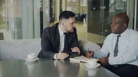 Två multiethnical partners i formell kläder som ser den digitala minnestavlan och diskuterar deras affärsidéer på en tabell lager videofilmer