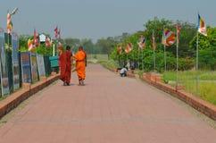 Två munkar går på vägen i Lumbini, Nepal - födelseort av Buddha royaltyfri fotografi