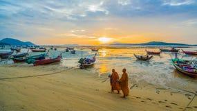 två munkar som går allmosa på stranden arkivbild
