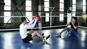 Två muskulösa mandrev i idrottshallen som gör tillsammans skjuta-UPS för mage och kastar den tunga sportive bollen under lager videofilmer