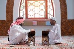 Två muslimmän som läser Koranen i moskén fotografering för bildbyråer