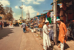 Två muslimmän som möter och talar på marknadsgatan med klädstrores Arkivfoton