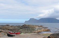 Två mycket lilla fisherfartyg på de steniga kusterna av Gjogv, Faroe Islan Royaltyfria Bilder