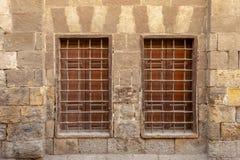 Två närgränsande träfönster med järnraster över den dekorerade stentegelstenväggen, medeltida Kairo, Egypten royaltyfri fotografi