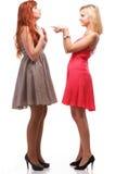 Två nätt kvinnor som är ljust rödbrun med blondin i kappor på vit Royaltyfria Foton