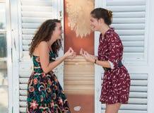 Två nätta flickor gör det italienskt vad är dig som omkring talar? tecken royaltyfria bilder