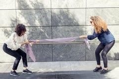 Två nätta flickor improviserar en dragkamp med en halsduk Royaltyfria Bilder