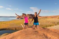 Två nätta flickor som hoppar för glädje Fotografering för Bildbyråer
