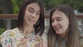 Två nätta flickor som sitter utomhus tillsammans att prata om ny manikyr och att visa fingrar och, spikar Flickvänsamtal lager videofilmer