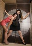 Två nätta flickvänner på partidansen som tätt ler upp, utsmyckat mode, klär royaltyfri fotografi
