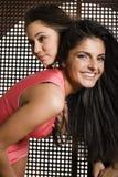 Två nätta flickvänner på partidansen som tätt ler upp, utsmyckat mode, klär royaltyfria bilder