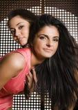 Två nätta flickvänner på partidansen som tätt ler upp, utsmyckat mode, klär fotografering för bildbyråer