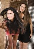 Två nätta flickvänner på partidansen som tätt ler upp, utsmyckat mode, klär idérik inre bakgrund royaltyfri fotografi
