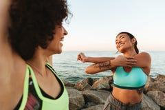 Två nätta konditionkvinnor som utomhus sträcker henne händer Arkivfoton