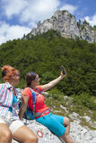 Två nätta kvinnliga kvinnor som fotograferar en selfie på bergmaximum arkivbild