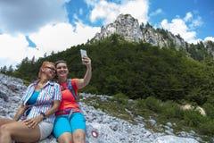Två nätta kvinnliga kvinnor som fotograferar en selfie på bergmaximum royaltyfri fotografi