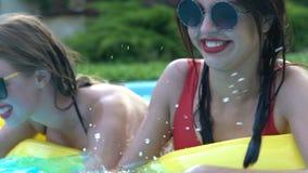 Två nätta kvinnor som har gyckel i simbassängen, plaskande vatten på de lager videofilmer