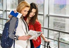 Två nätta kvinnor som står i terminalen med en resväska, en ryggsäck och en blick på översikten Arkivbild