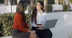 Två nätta kvinnor som utomhus delar en bärbar dator Arkivbilder
